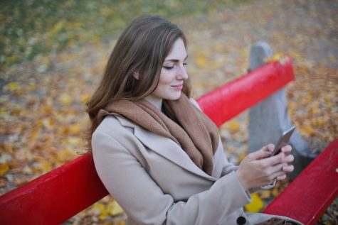 Brunette woman sitting on a red coloured park bench using a mobile phone